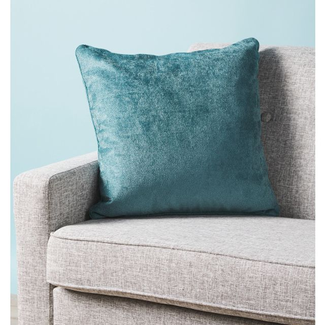A blue velvet pillow on a grey couch