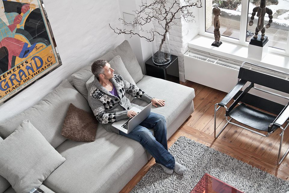 Man sitting on sofa with laptop in loft