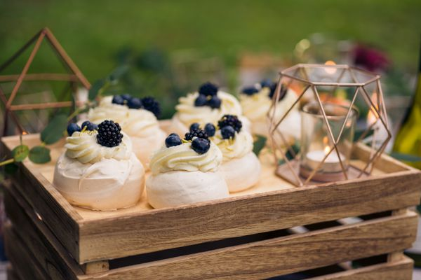 Mini pavlovas with mascarpone filling and berries at a relaxed, rustic outdoor wedding reception.