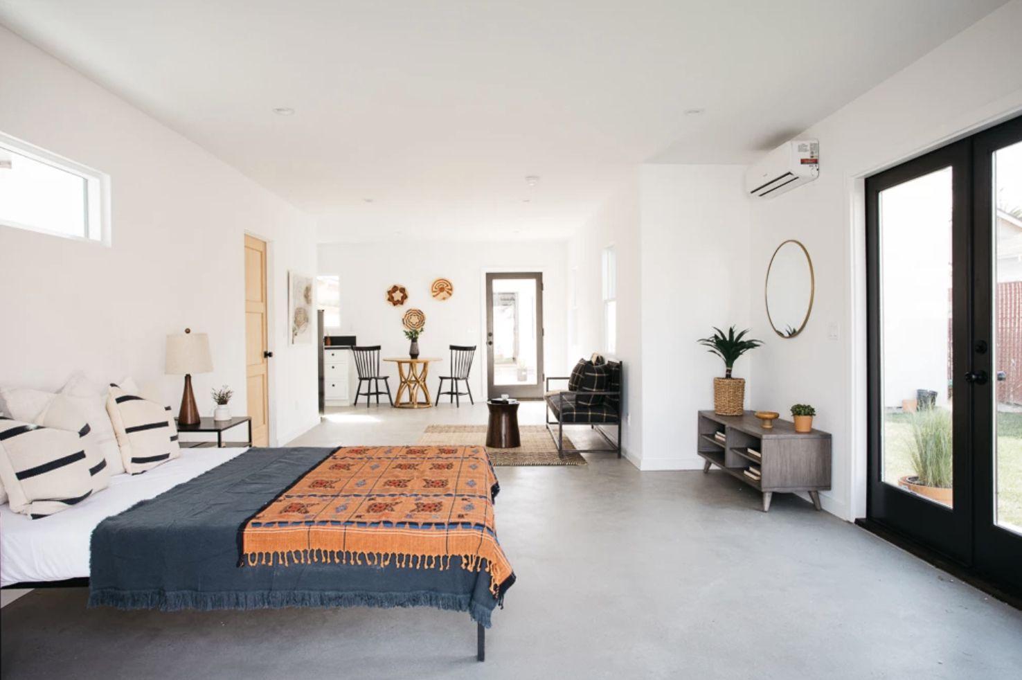 bedroom with open layout, navy blue bedspread, concrete floor, natural light