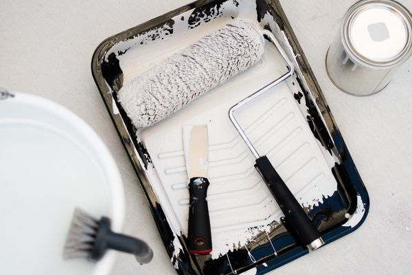 Black painting tray with white paint, roller and putty knife on top