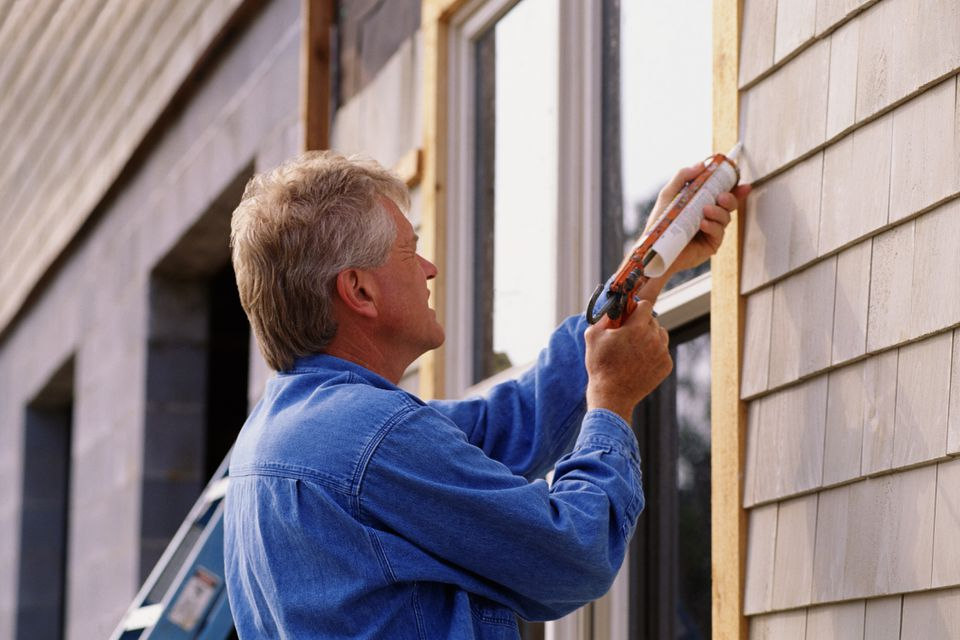 Man caulking around window
