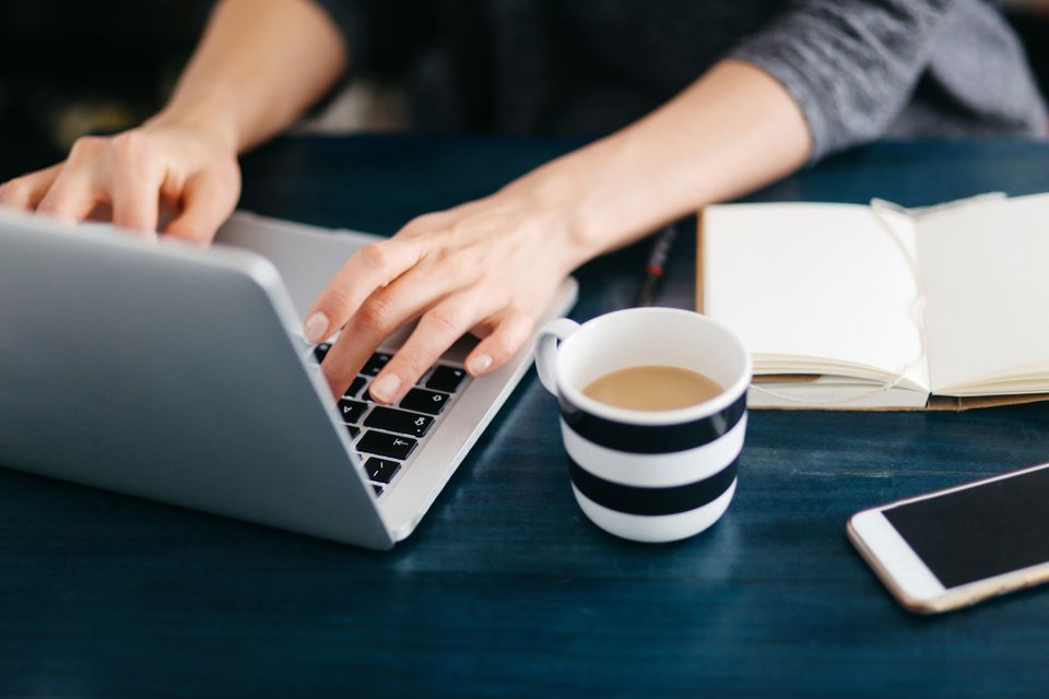 Woman freelancer or blogger writing on the laptop
