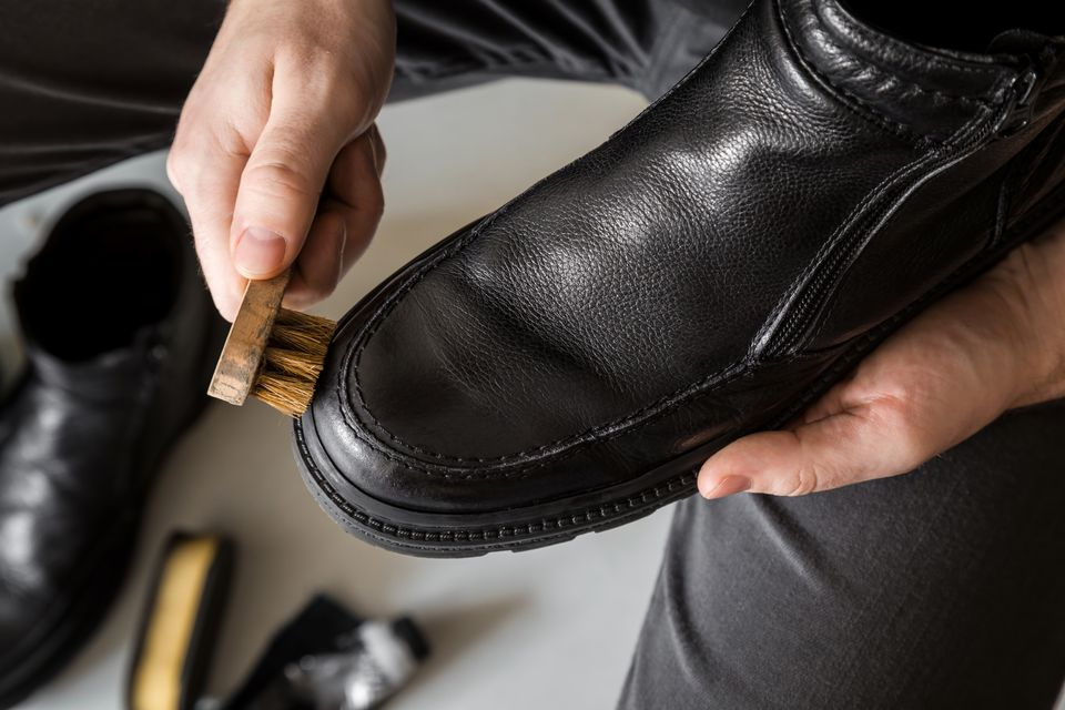 Man's hand cleaning elegant leather boots with brush. Cares about boots beauty and protection from cold and wet. Preparing for autumn and winter season. Footwear cleaning concept.