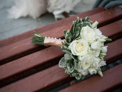 The bride's beautifully decorated bouquet of white roses and green leaves lies on a brown wooden bench. Wedding theme.