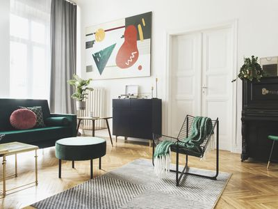 Sunny luxury home interior with design velvet sofa, armchair, tables, pouf, commode and accessroies. Nice plants on the piano. White walls with painting. Big windows. Stylish decor of sitting room