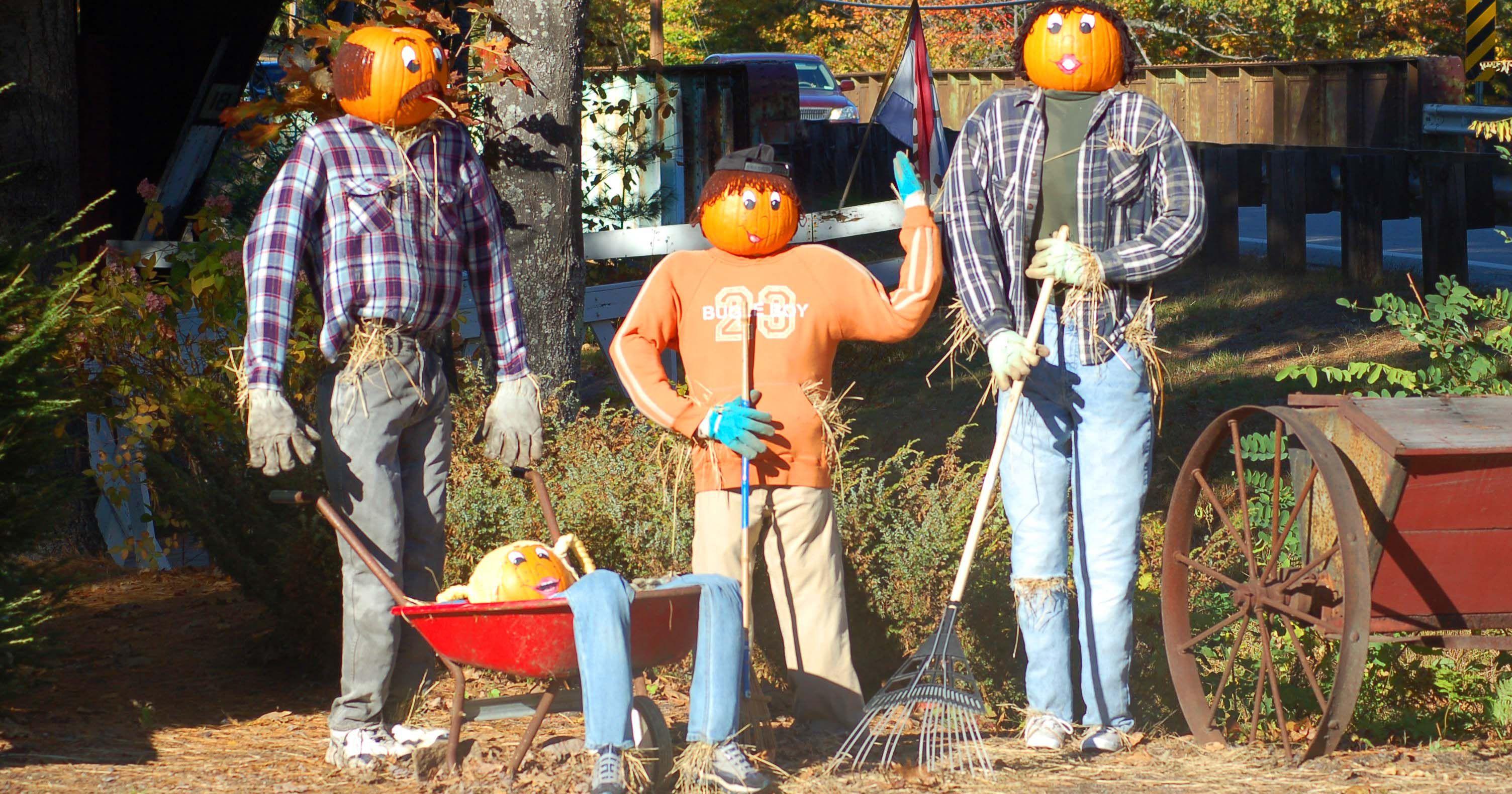 three scarecrows doing yard work