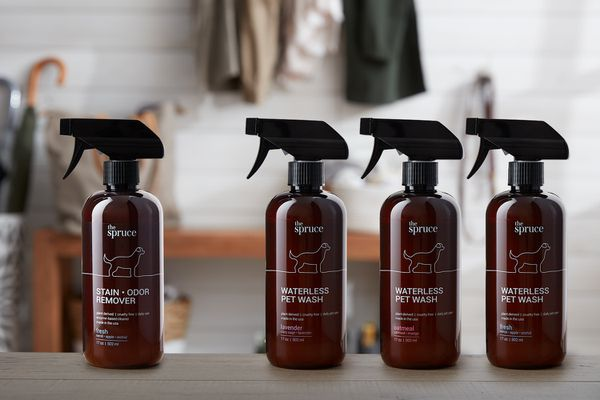 Amber bottles of stain and odor remover and waterless pet wash sprays in a mudroom