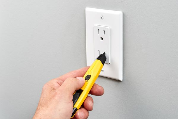 Yellow circuit tester inserted into standard 120-volt outlet receptacle