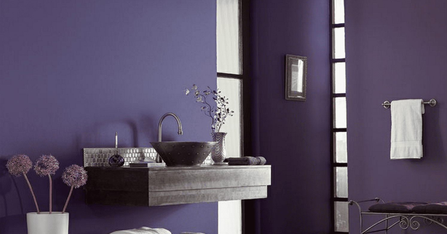 A jewel tone bathroom with purple walls and a hanging wall-mounted sink.