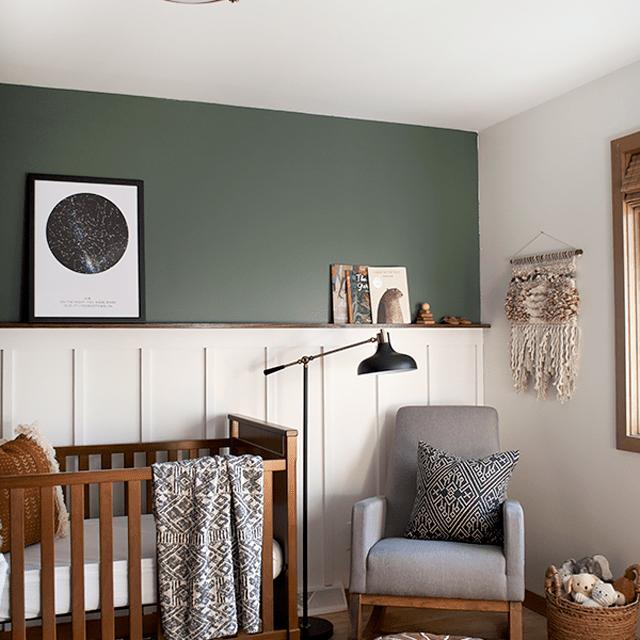 Vintage boho nursery with dark green accent wall