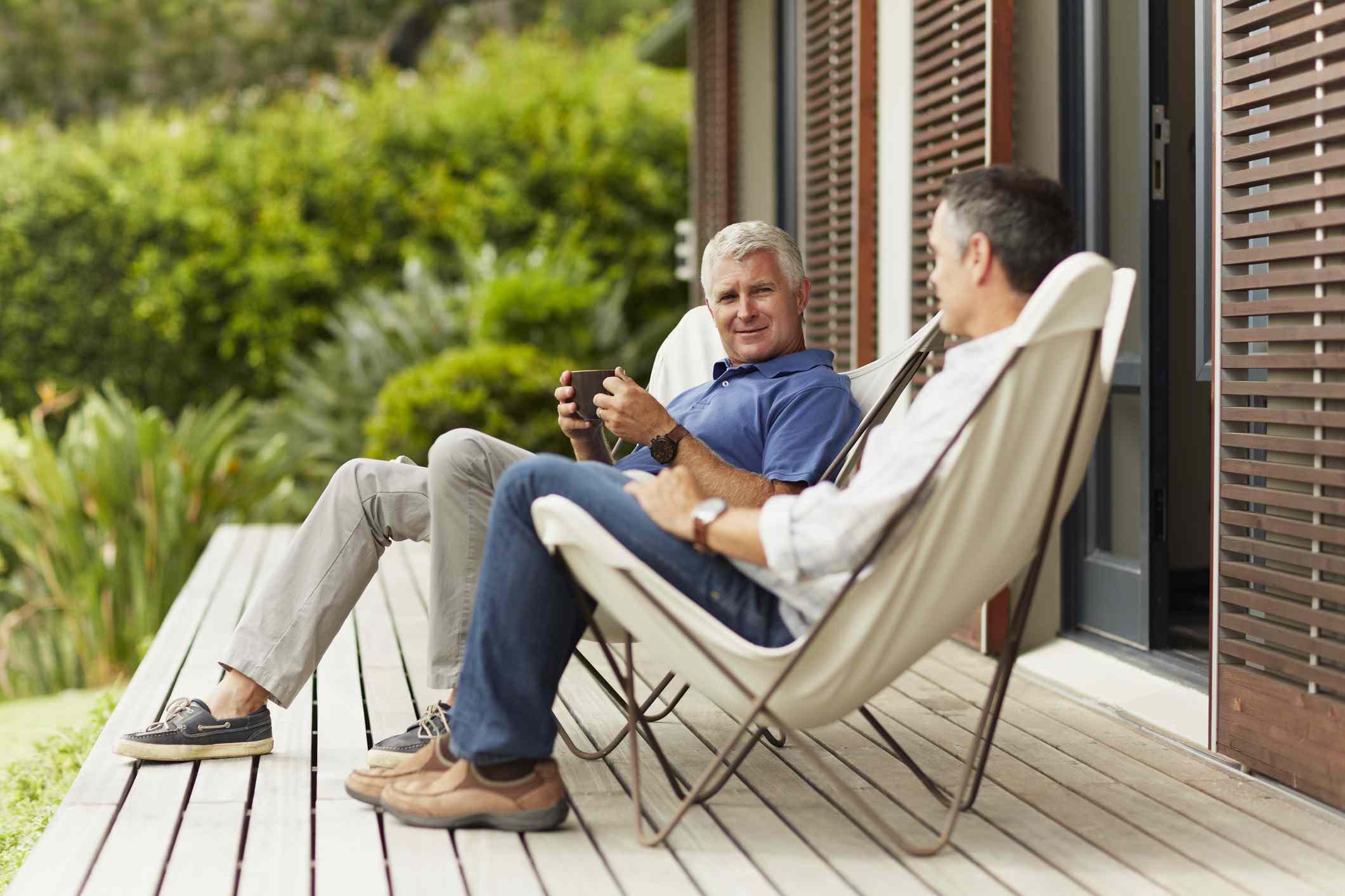 Dos hombres en una terraza sentados en sillas