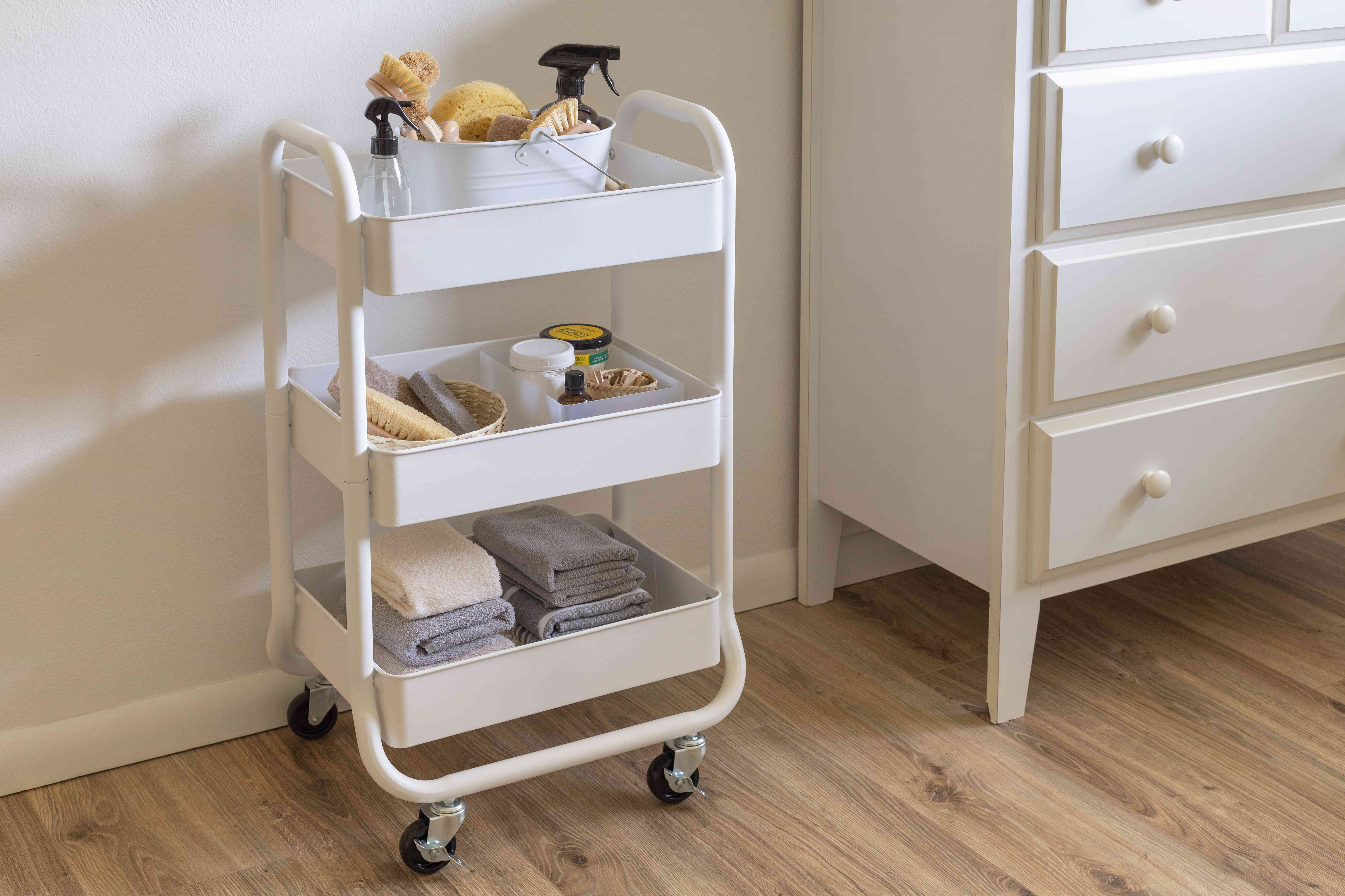 Moveable cart with wheels storing folded towels and cleaning supplies