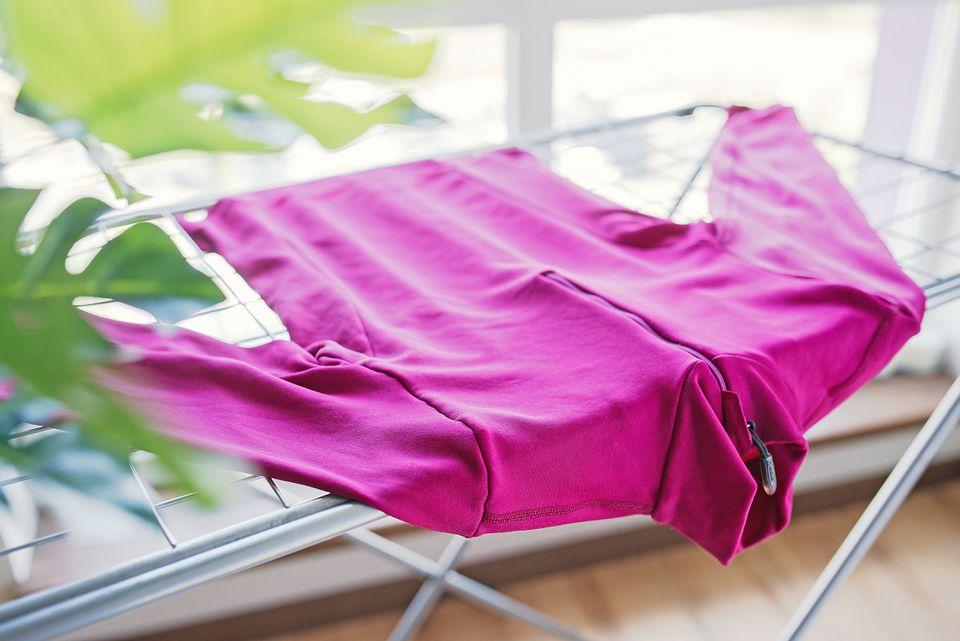 Pink fleece jacket lying on a metal drying rack