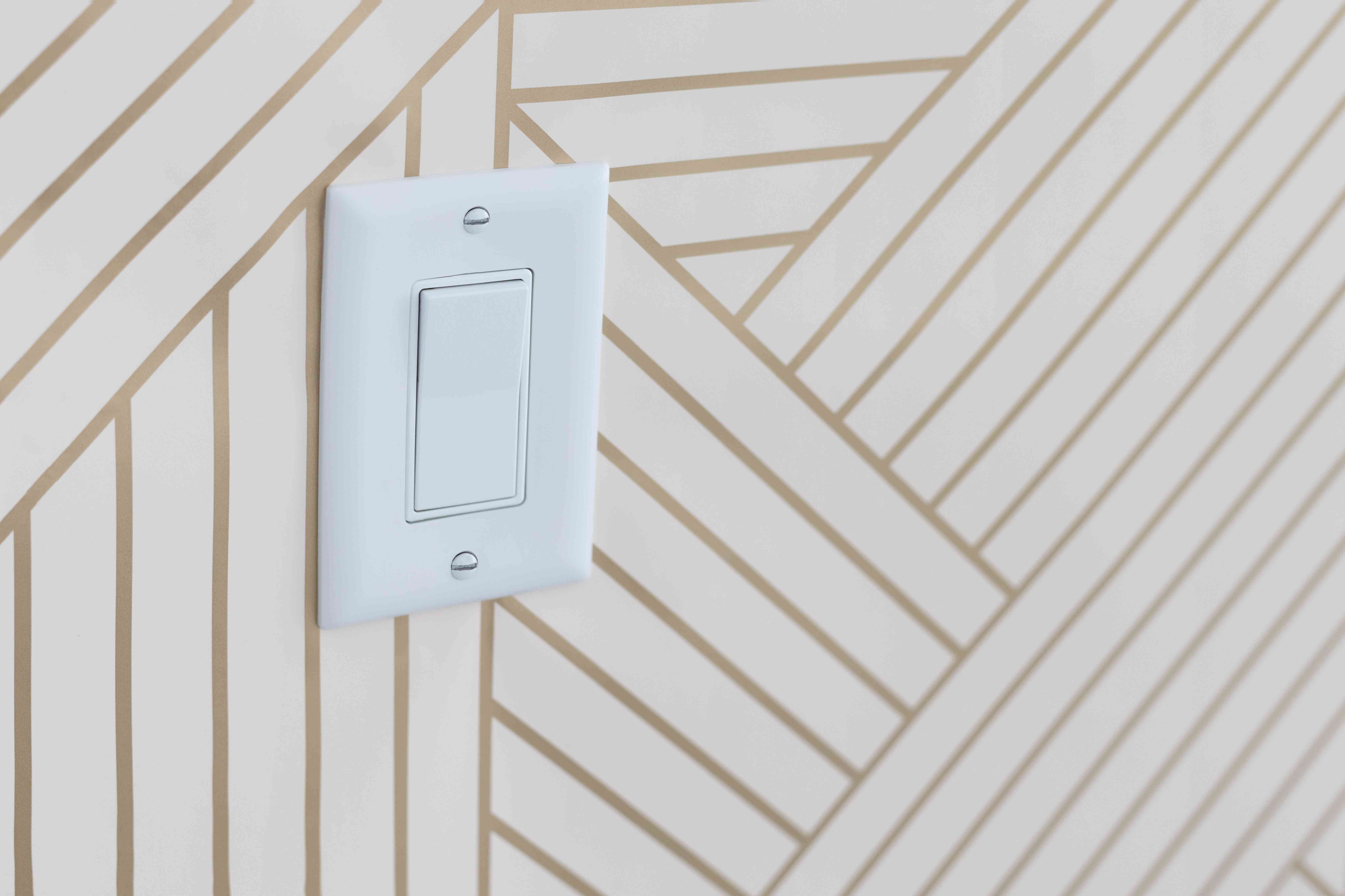 Light switch plate surrounded with white and gold striped wallpaper