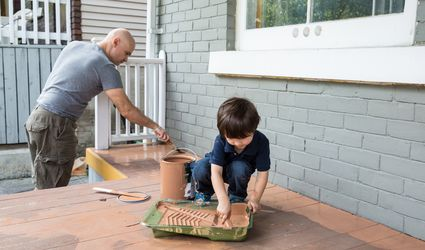 father and son painting deck