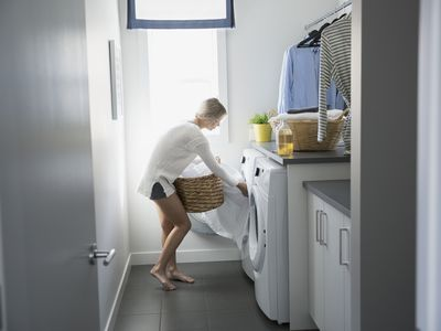 Woman removing sheets from dryer in laundry room