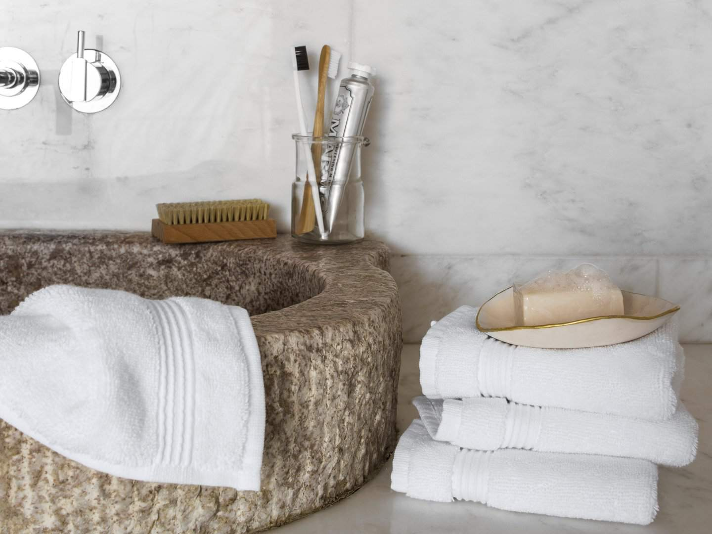 Parachute washcloths and hand towels surrounding a sink with other bathroom accessories