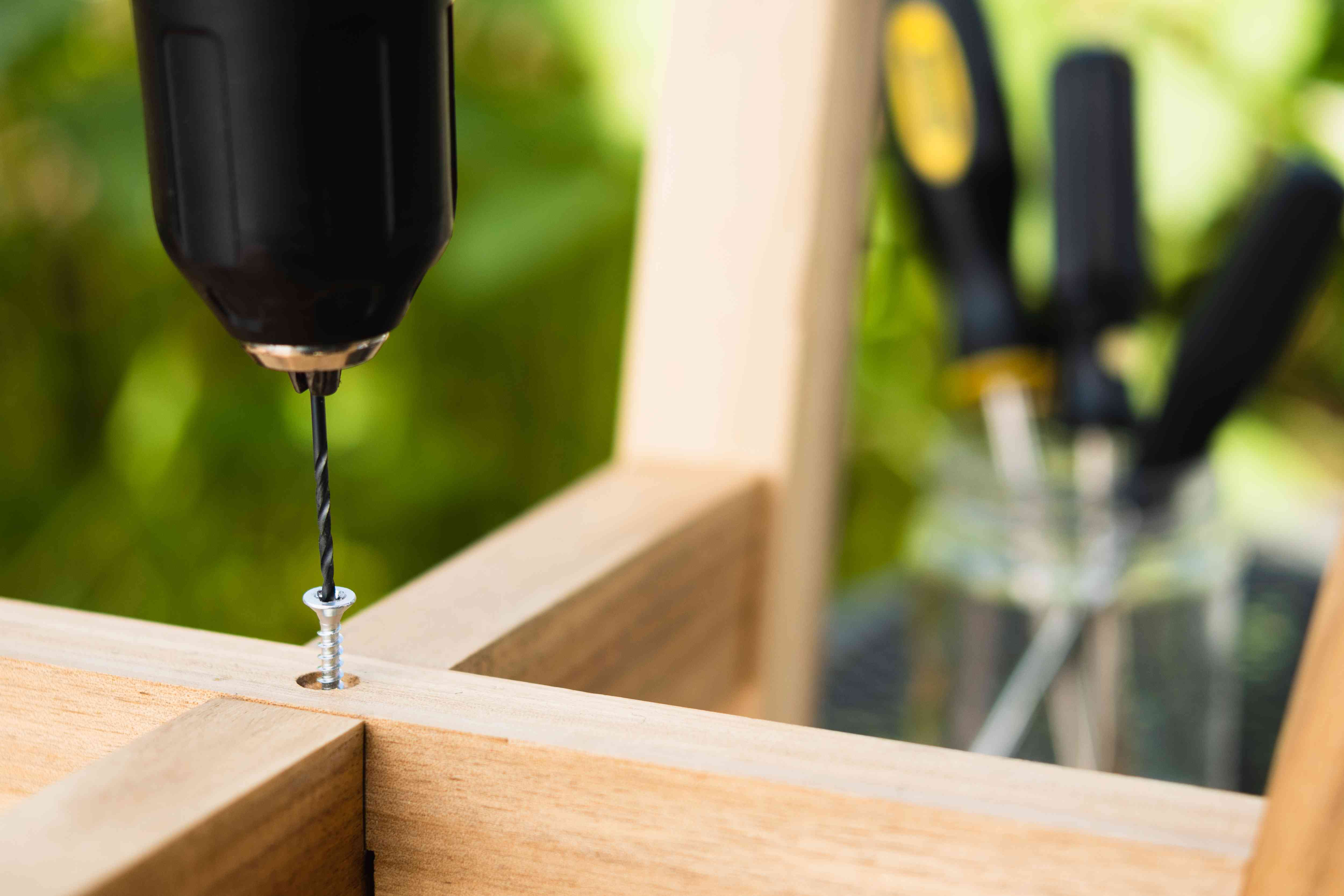 Electric drill drilling into stripped screw in wooden fixture
