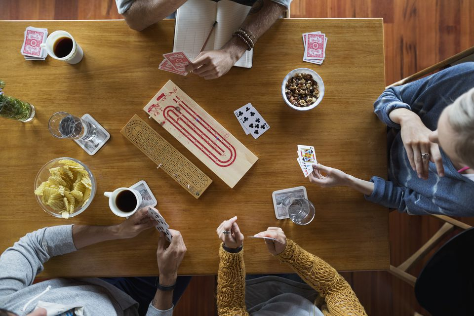 People playing a card game around a table with snacks
