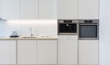 Small modern white kitchen with wall oven next to built-in wall espresso maker.