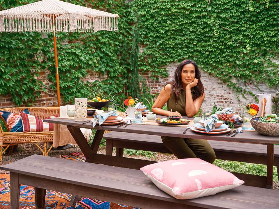 Padma Lakshmi poses in an outside dining area featuring entertaining items she curated for Etsy