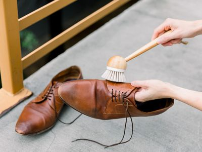 Someone cleaning brown leather shoes with a brush
