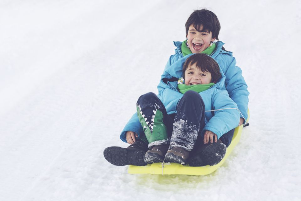two brothers on toboggan on snow covered hill