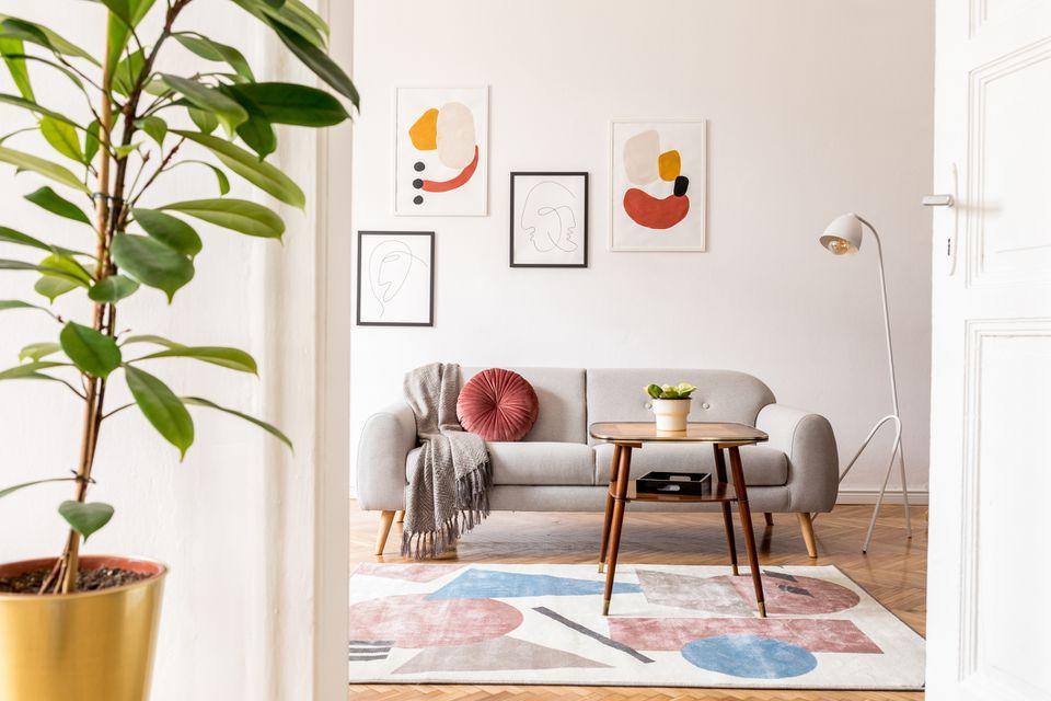 Elegante sala de estar retro con sofá de diseño gris, mesa de café, lámpara, plantas y muebles. Simulacros de carteles enmarcados en las paredes blancas. Habitación minimalista con parquet de madera marrón y lámpara de diseño.
