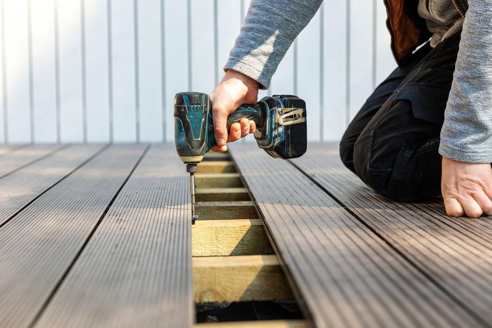 terrace deck construction - man installing wpc composite decking boards