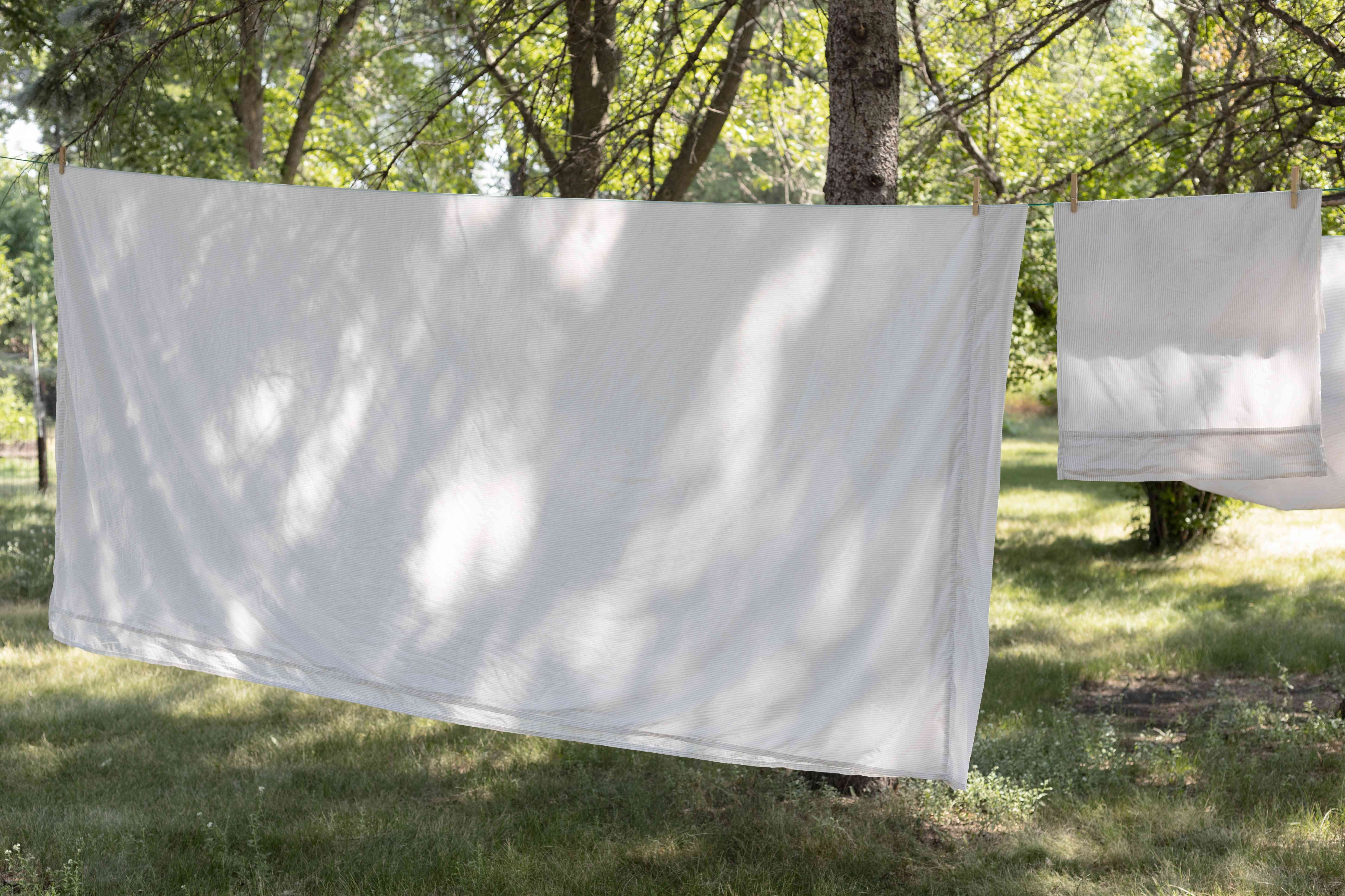White sheets and towels being line dried to lower electricity bill