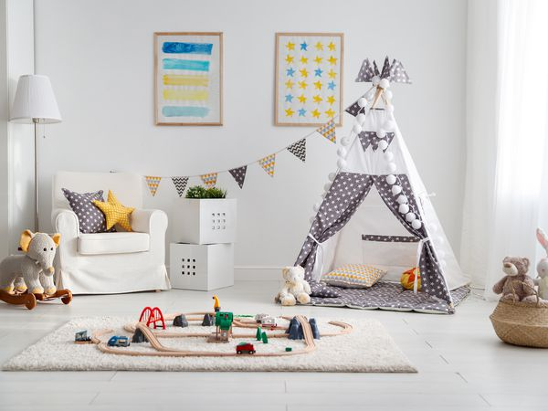 empty children's playroom with tent and toy railway