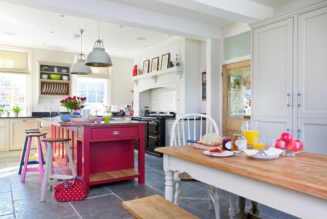Cocina con isla roja, taburetes de bar y mesa de cocina larga . Paredes y electrodomésticos de cocina turquesa retro con puerta roja y taburetes
