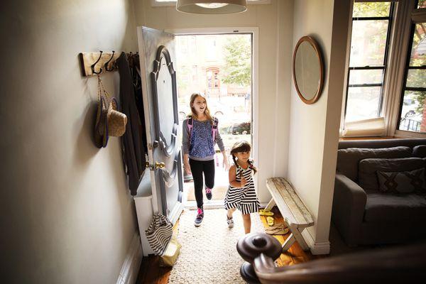 Sisters entering home entryway