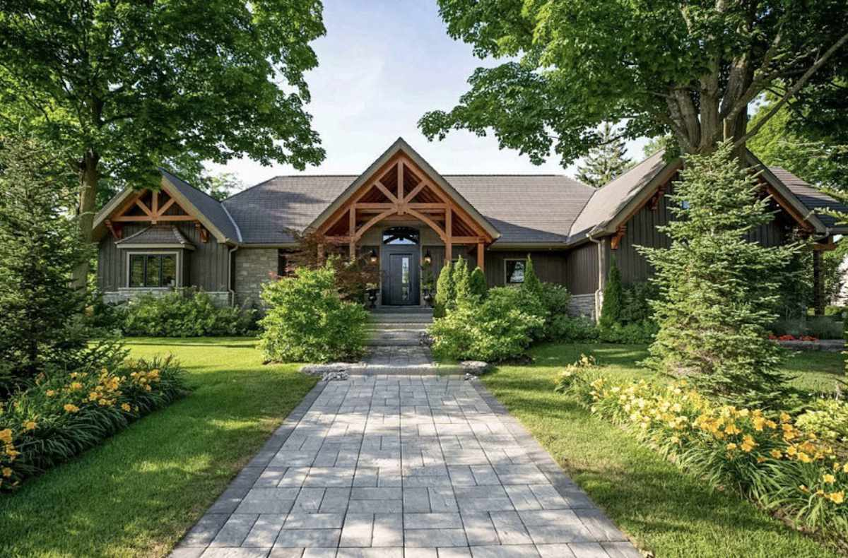 front yard with rustic home, cement walkway, balanced landscaping
