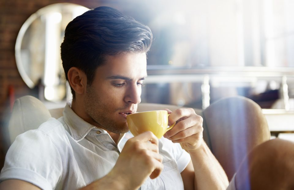 A man in a cafe drinking coffee