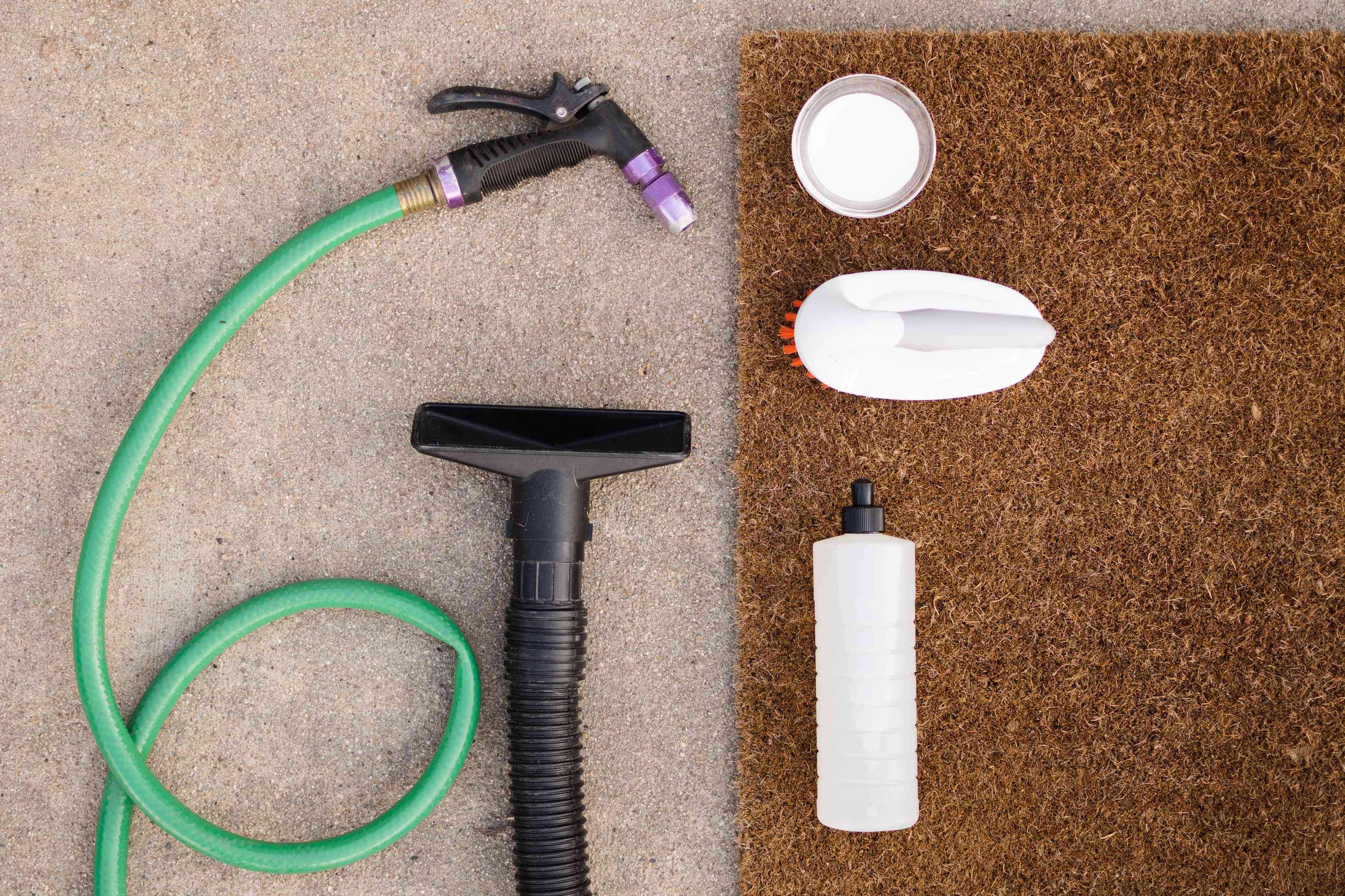 Materials for cleaning a doormat laying on tan carpet and brown doormat