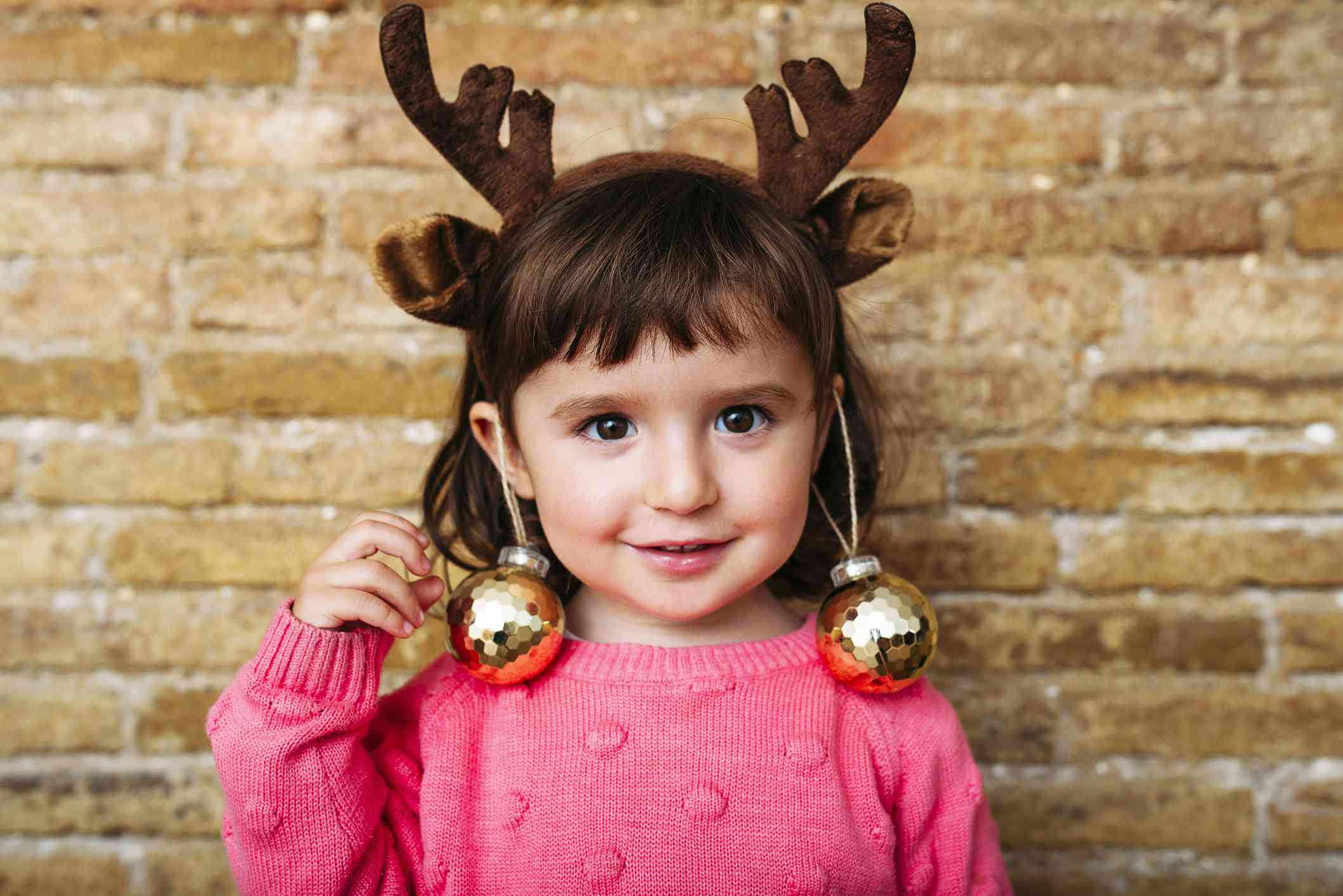Portrait of smiling toddler girl wearing reindeer antlers headband and Christmas baubles