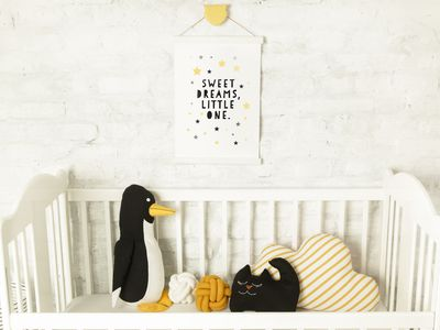White wooden baby crib and toys in the room, Scandinavian inspired kids room interior