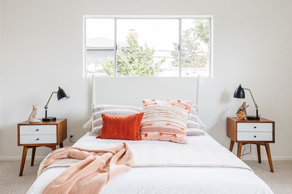 Minimalist bedroom with white walls, white bed with red cushions and two wooden night stands with white shelves