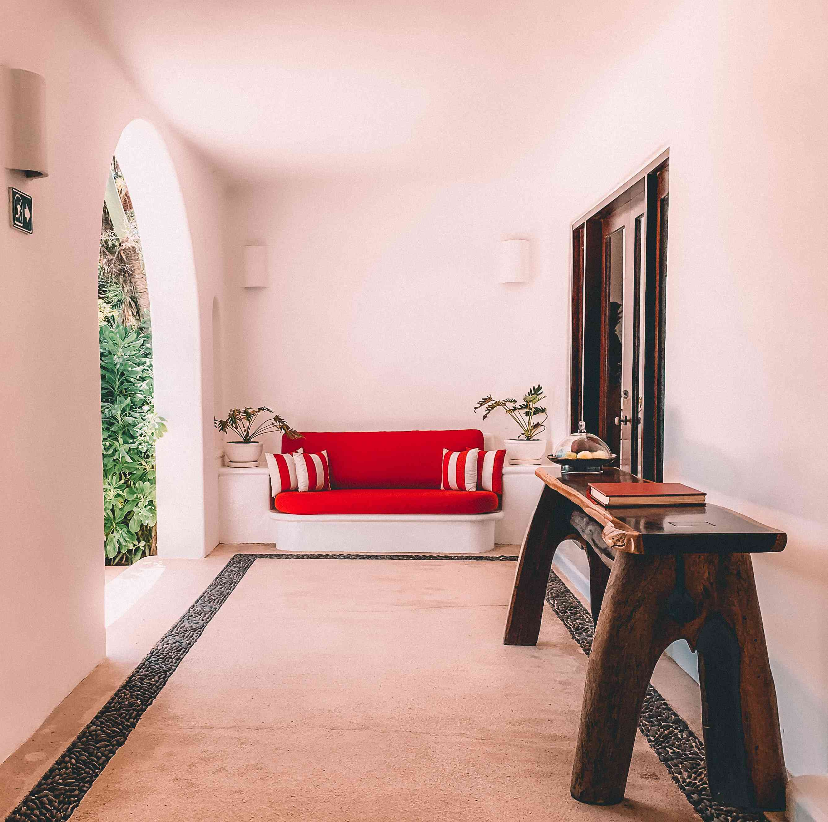 brown wood table with bright red sofa