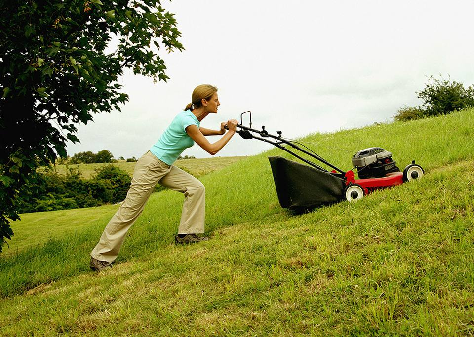 Woman mowing grass uphill.