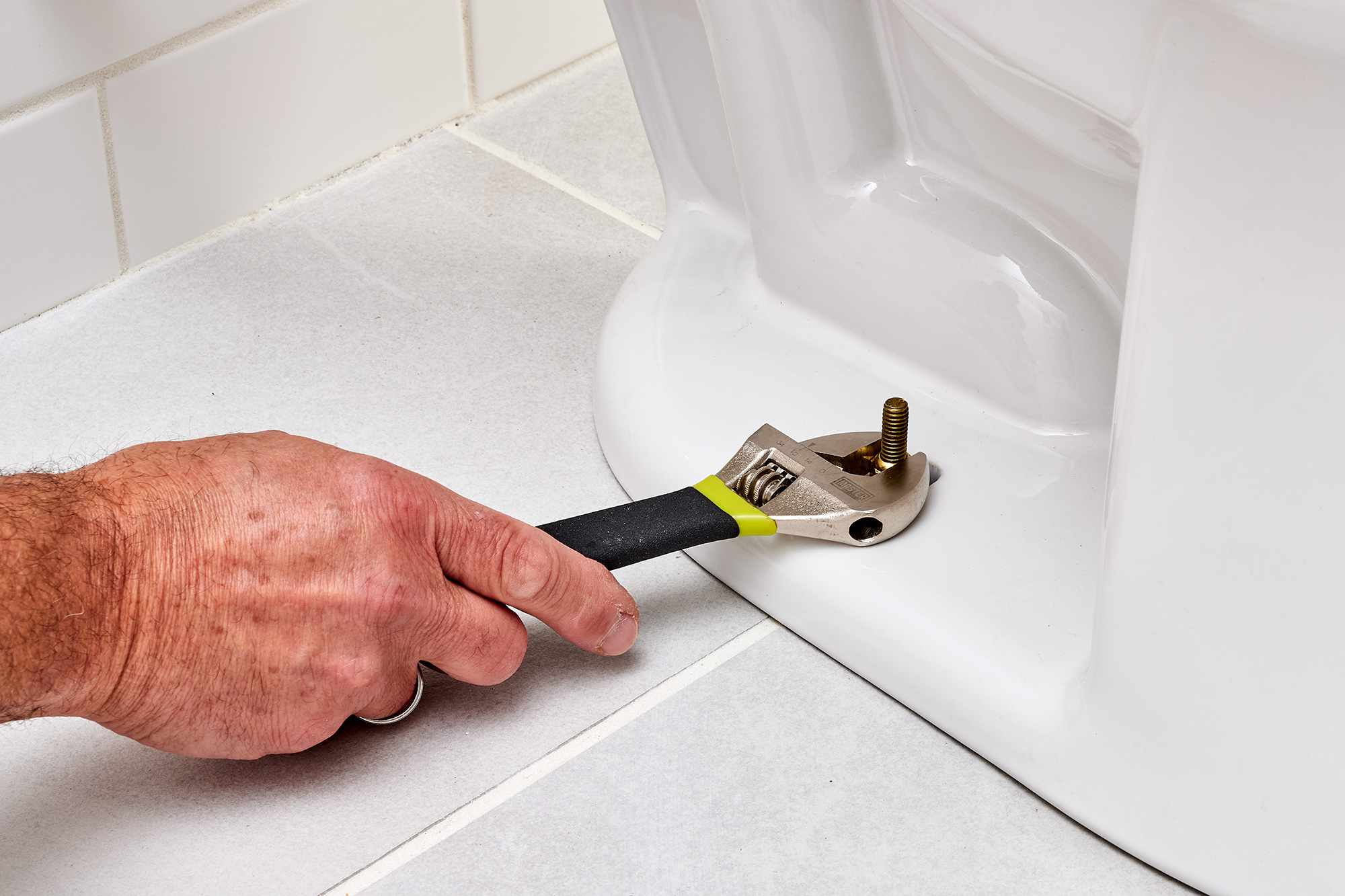 Bolts tightened with wrench to secure toilet to floor