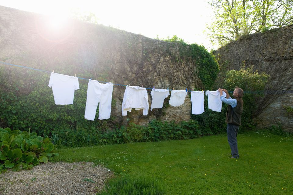 Man hanging up laundry on washing line in a garden