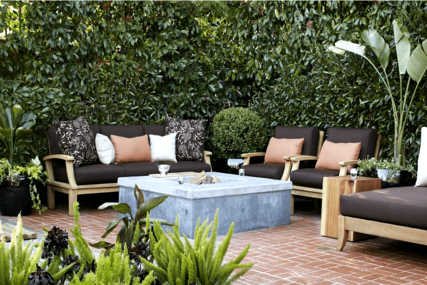 Patio area with several chairs and couches and fire pit adorned with lush green walls.