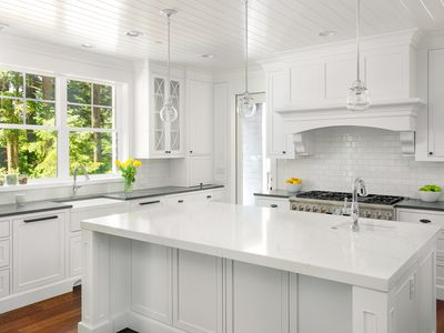 Monochromatic white kitchen with subway tile backsplash and marble countertops