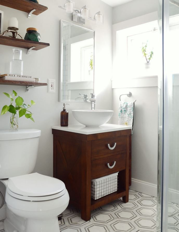 Updated bathroom with geometric tile flooring and light gray walls.