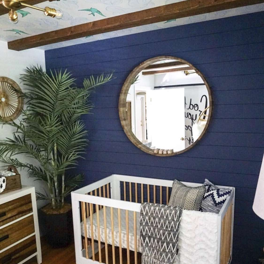 wallpaper mural used on the ceiling of a nursery, that also features painted shiplap, wood beams, and a large mirror
