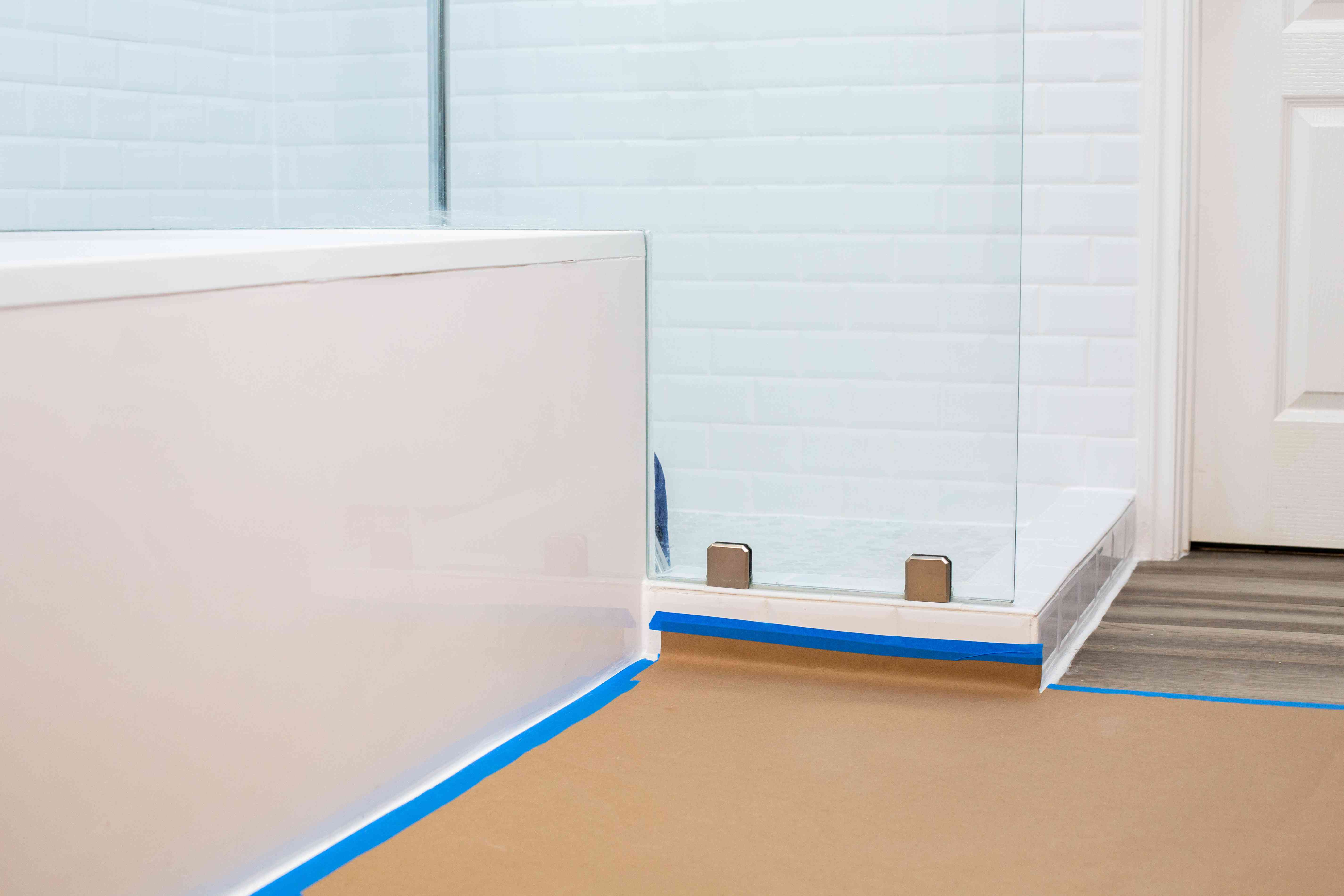 Blue tape and kraft paper masking floor areas in bathroom