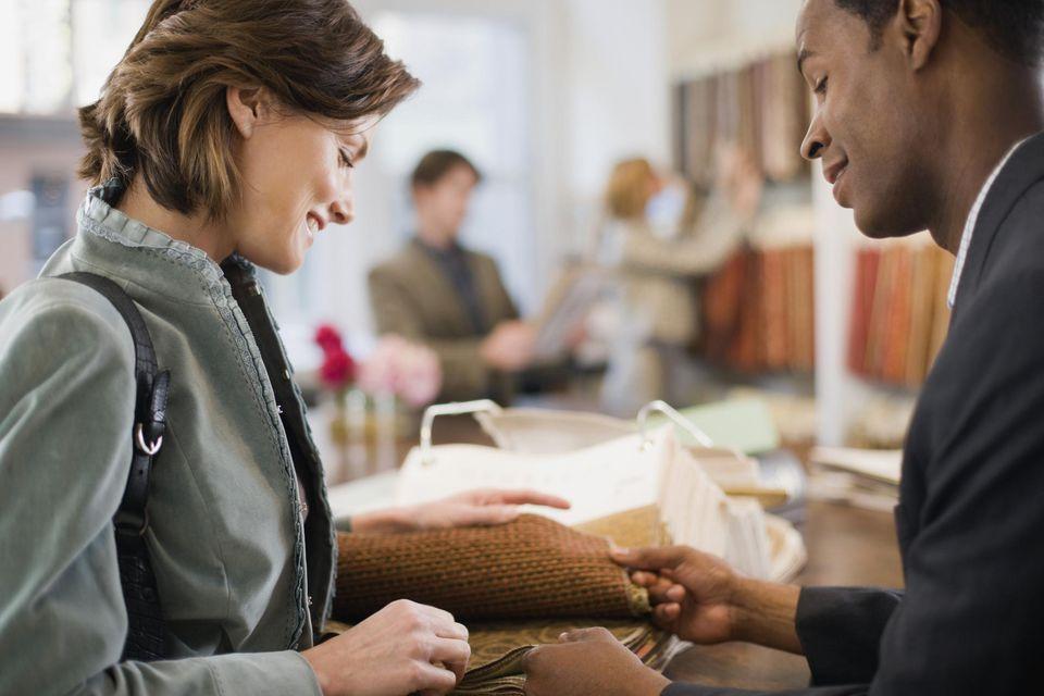 Salesman Showing Woman Carpet Samples